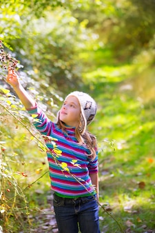 Kid winter girl picking mulberry berries in the forest