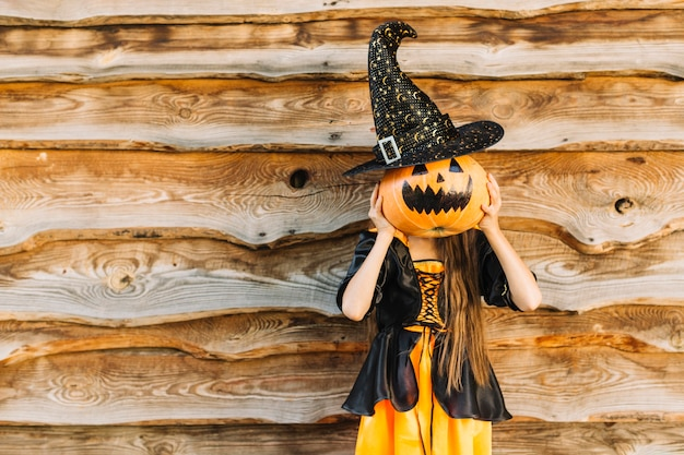 Kid in witch clothes closing face by pumpkin with hat