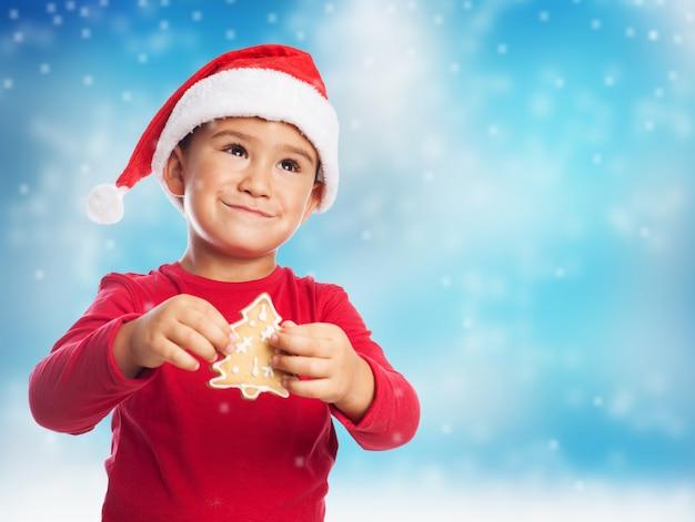 Ребенок с деревом печенья и шляпу санта клауса