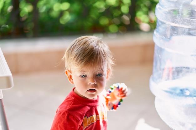 손에 딸랑이를 들고 있는 아이가 정수기 근처 발코니에 서 있다