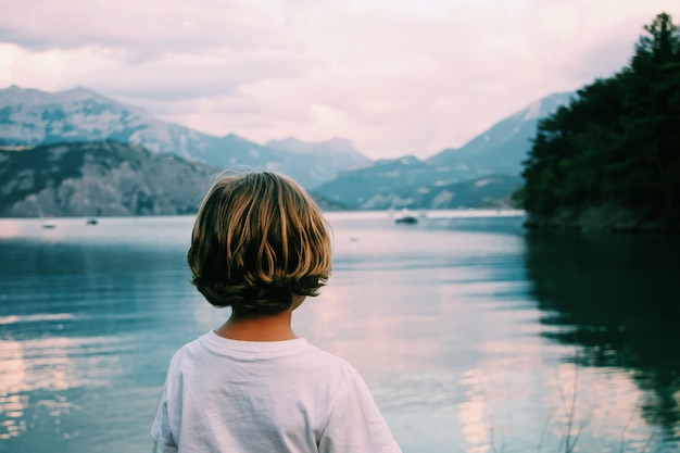 Kid with blonde hair looking at the sea with mountains in the distance shot from behind