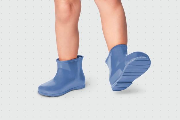Bambino con il colpo dello studio degli stivali di gomma blu