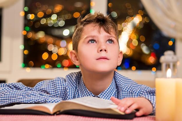Малыш с книгой возле свечи. ребенок трогательно книгу рядом с окном. загадывать желание на рождество. праздник его вдохновляет.