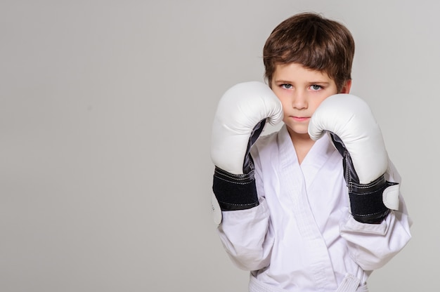 Kid with boxing gloves poses in studio