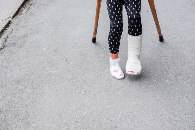 Kid with broken leg is on crutches on the street. conceptual photo depicting a child with a broken leg on a holiday, on the school holiday.girl injured in feet has bandage with crutches on asphalt