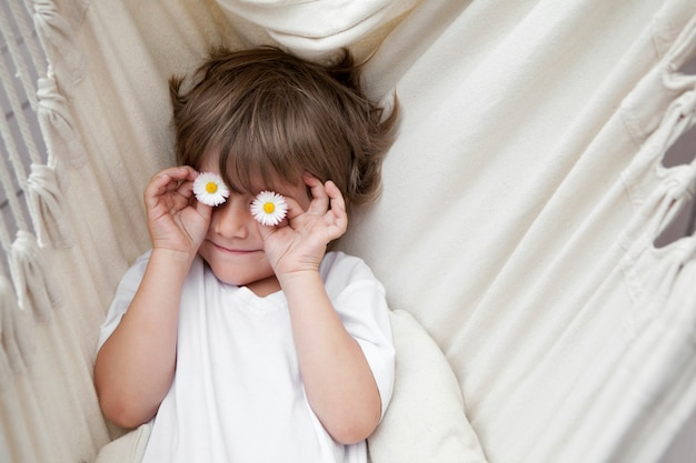 Kid with chamomile flowers near his eyes lying on hammock in a white t-shirt. summer vacation