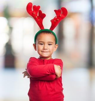 Kid with crossed arms and plush reindeer antlers