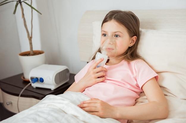 ネブライザーマスク付きのベッドに横たわっている嚢胞性線維症の子供