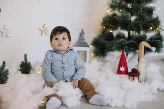 Kid with dark hair in a shirt sits under a christmas tree in a festive interior with lanterns, gnomes, stars and garland lights.