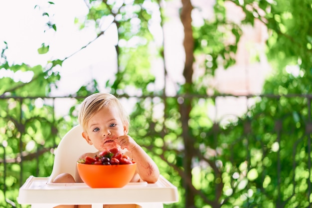 Kid with a dirty face sits on the balcony and holds cherries in his hands