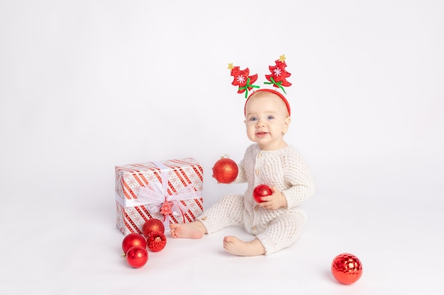 Kid with gift and christmas balls on white isolated background, space for text, new year and christmas concept