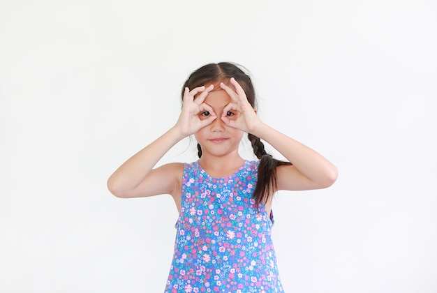 Kid with hands glasses in front of her eyes isolated on white wall