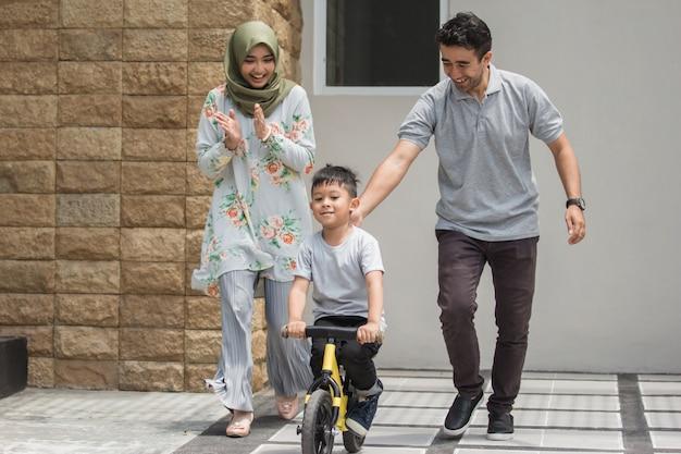 自転車に乗る方法を学ぶ父親と子供