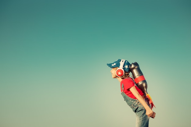Kid with jet pack against autumn sky background child playing outdoors leader and winner concept