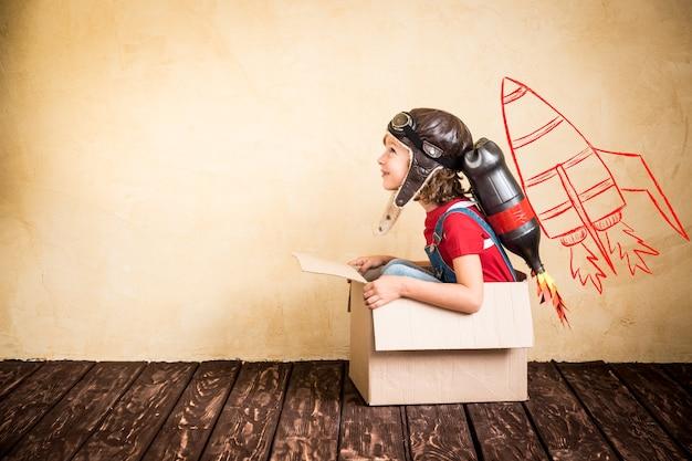 Малыш с реактивным ранцем. ребенок играет дома. концепция успеха, лидера и победителя
