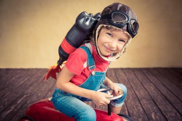 Малыш с реактивным ранцем за рулем ретро игрушечной машины. ребенок играет дома. концепция успеха, лидера и победителя