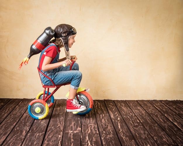 Малыш с реактивным ранцем на велосипеде. ребенок играет дома. концепция успеха, лидера и победителя