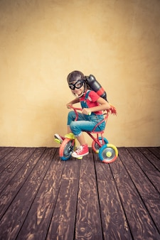 Kid with jet pack riding bike. child playing at home. success, leader and winner concept