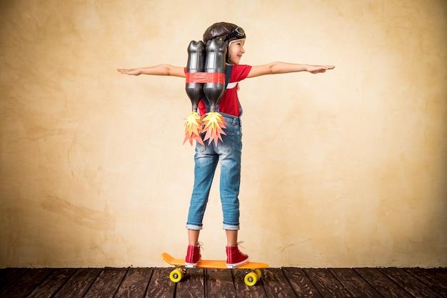 스케이트 보드를 타고 제트 팩을 가진 아이. 집에서 노는 아이. 성공, 지도자 및 승자 개념