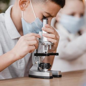 Малыш с медицинской маской, глядя в микроскоп крупным планом