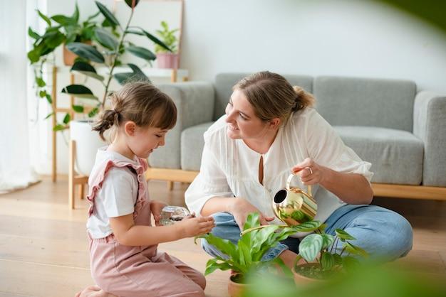 家で鉢植えの植物に水をまくお母さんと子供