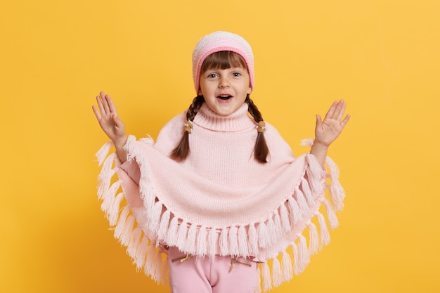 Kid with open mouth spreading hands in excitement, looks at front, wearing cap, knitted poncho and trousers