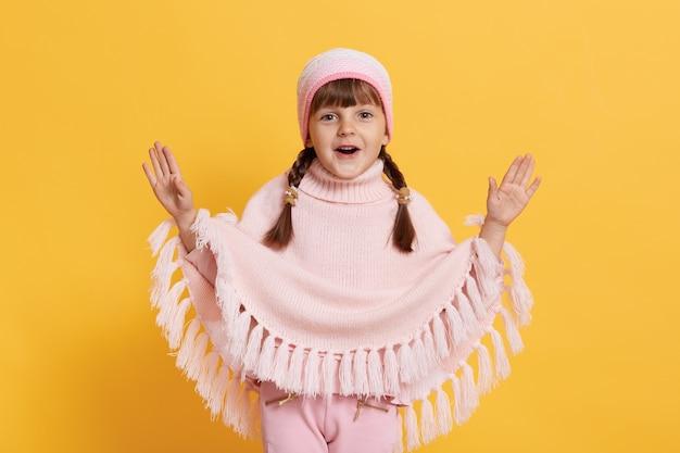 Ребенок с открытым ртом, разводя руками в возбуждении, смотрит вперед, в шапке, вязаном пончо и брюках