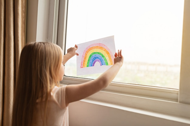 Kid with painted rainbow during covid-19 quarantine near window