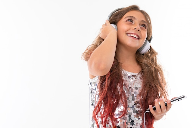 Kid with phone in her hands looks up and listens to music in headphones
