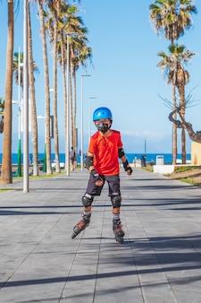 ローラースケートに乗っている保護フェイスマスクを持つ子供
