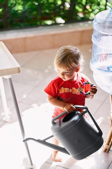 Kid with a rattle and a watering can in his hands stands on the balcony near the water cooler