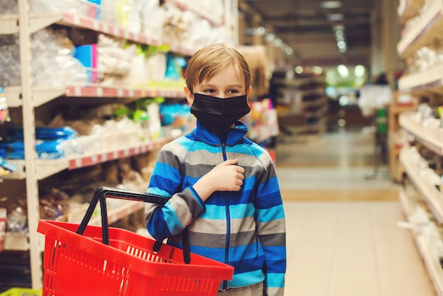 Kid with shopping basket in supermarket. child wears protected mask in shop.