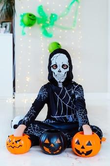 Малыш в костюме скелета паука делает трюк или угощает хэллоуин тыквенной корзиной
