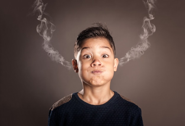 Kid with smoke on his ears on a gray