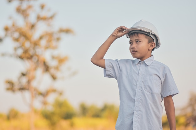 Kid with white hard hat outdoors