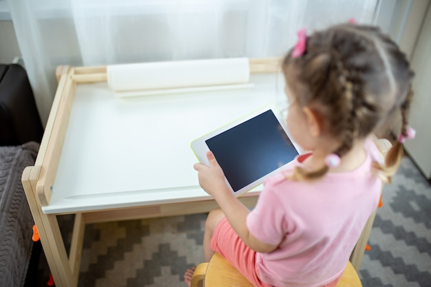 A kid with white tablet. kid on online education, e-learning while quarantine. kid watches cartoons on tablet.