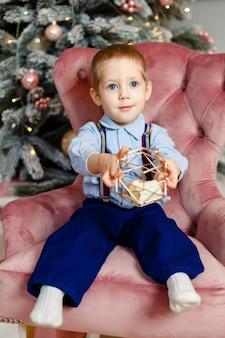 自宅でクリスマスプレゼントを持った子供。クリスマスツリーの下で遊ぶ小さな男の子