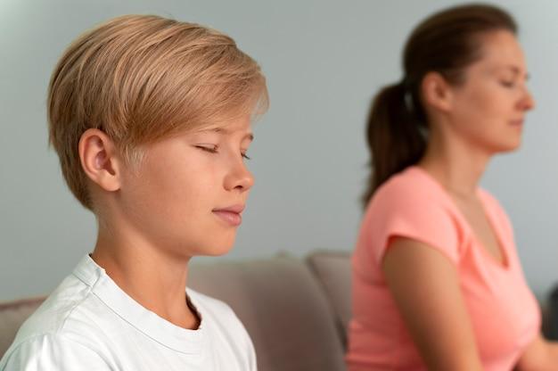 Kid and woman meditating close up