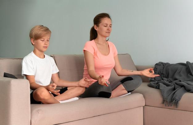 Kid and woman meditating full shot