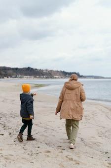 Bambino e donna in riva al mare a pieno tiro