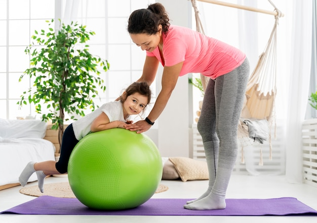 Kid and woman training with gym ball