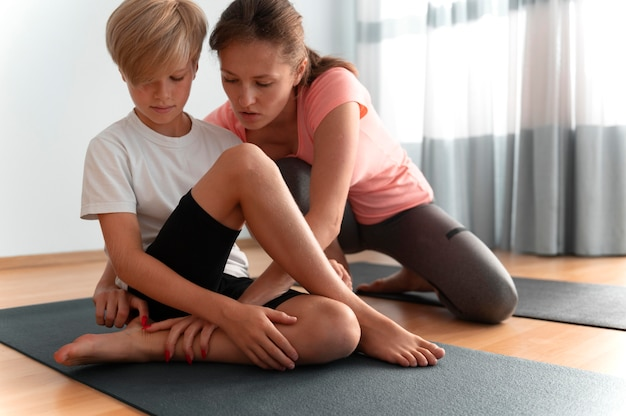 Kid and woman with yoga mats full shot