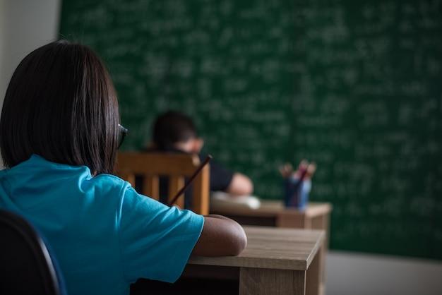 아이는 교실에서 책을 씁니다.