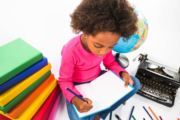 Kid writing in notebook in studio