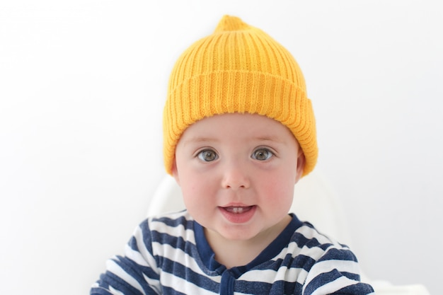 Kid in a yellow hat with two first teeth studio