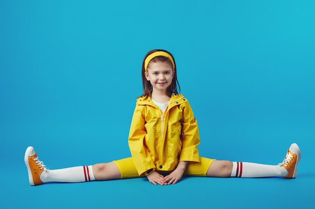 Kid in yellow outfit doing splits stretching exercise straight angle pose