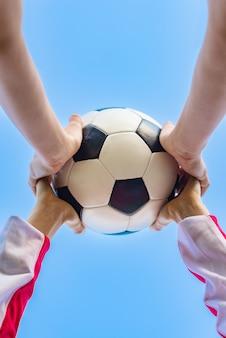 Руки ребенка и взрослого держат футбольный мяч на фоне неба