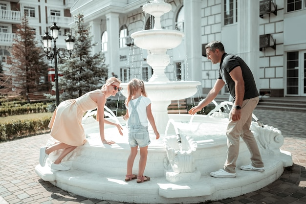 冗談です。美しい噴水の近くで水しぶきで遊んで楽しんでいる幸せな家族。