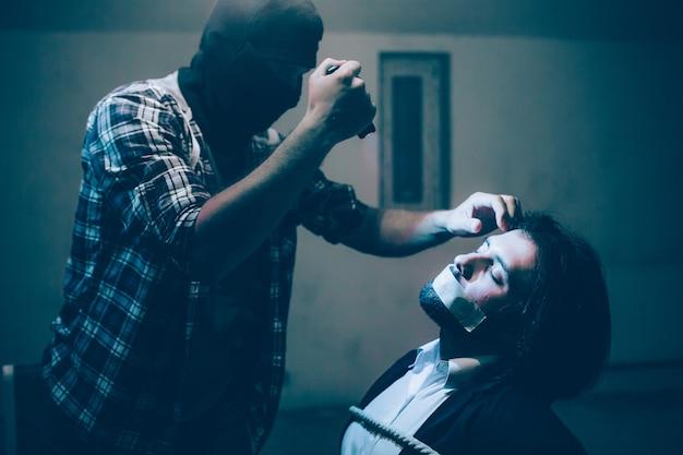 Похищенный бизнесмен сидит на стуле и связан веревками. он держит глаза закрытыми. убийца стоит перед ним и касается лба своей жертвы. также он держит в руке фотоаппарат
