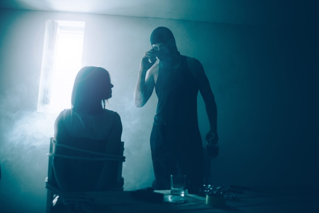 Kidnapper and his victim are in dark room with small window
